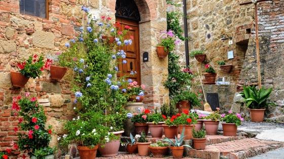 Ristrutturazioni casolari: casa in pietra con tanti vasi di fiori e piante vicino all'ingresso